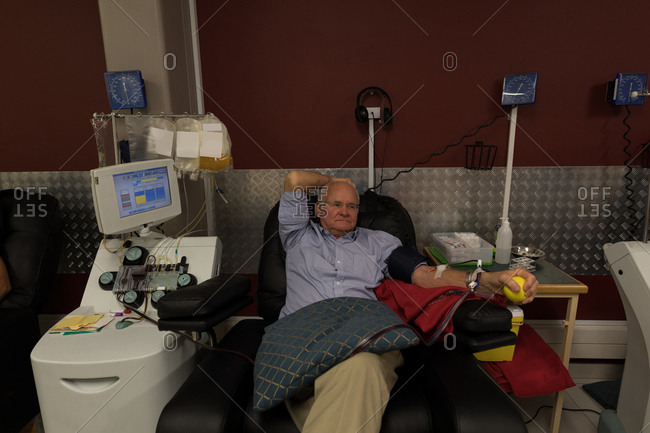 Active senior man donating blood in blood bank