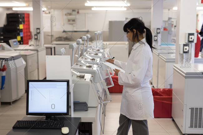 Laboratory technician writing on clipboard in blood bank