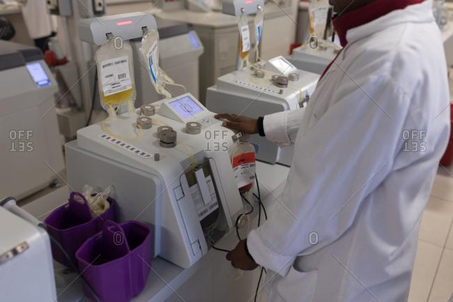 Laboratory technician using a machine in blood bank