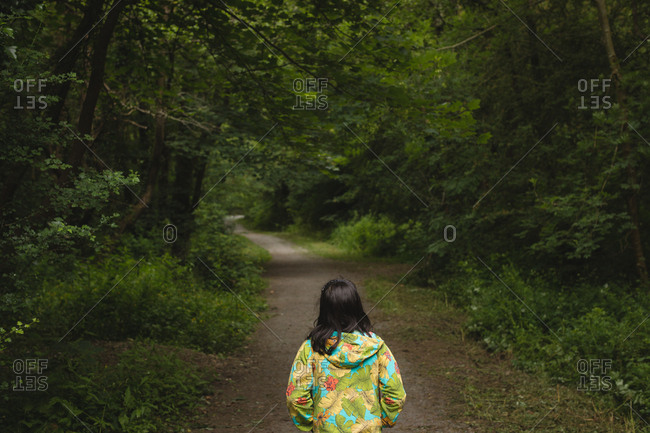 Rear view of girl standing alone in forest path