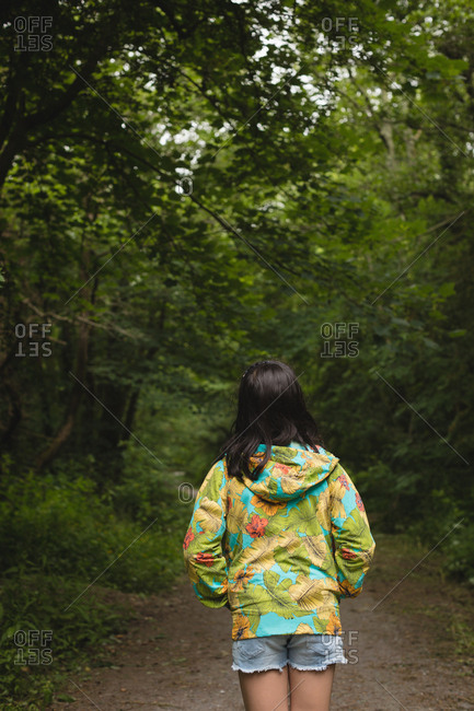 Young girl standing alone in forest path