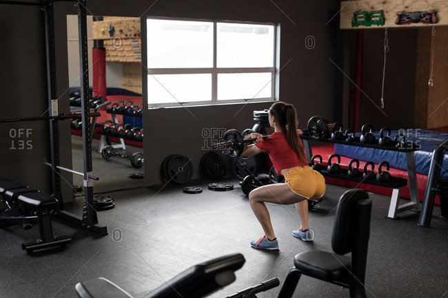 Rear view of woman lifting barbell in fitness studio