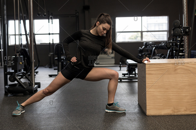 Fit woman doing stretching exercise in fitness studio