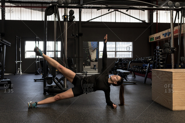 Beautiful woman doing side plank exercise in fitness studio