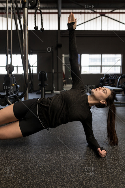 Young woman doing side plank exercise in fitness studio