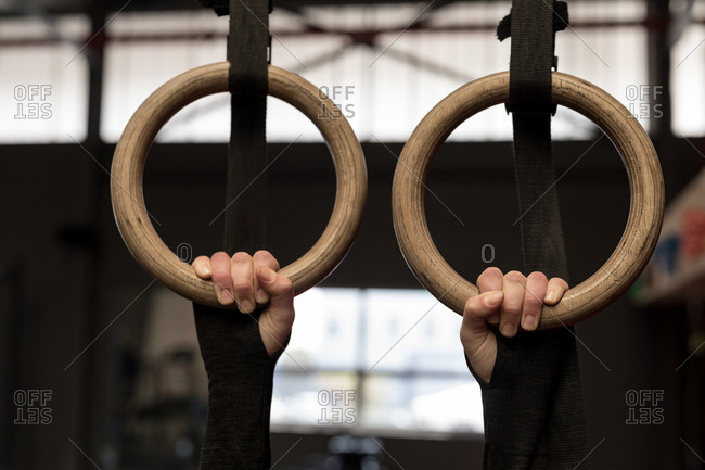 Fit woman exercising on gymnastic rings in fitness gym