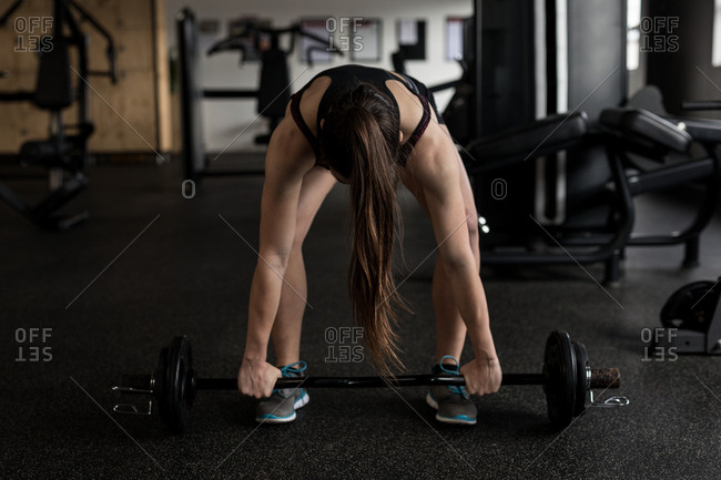 Fit woman lifting barbell in fitness studio