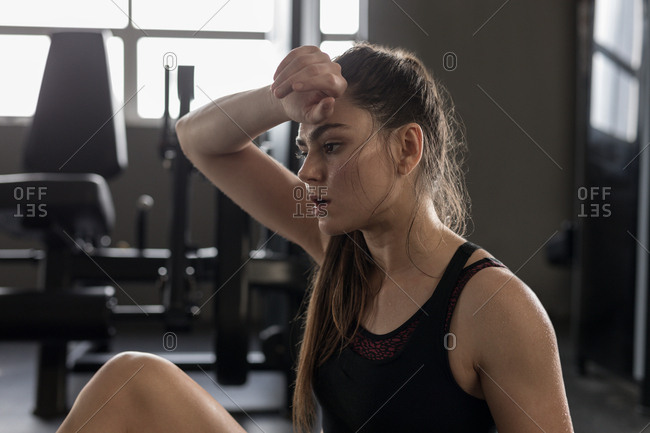 Young woman wipes sweat after workout in fitness studio