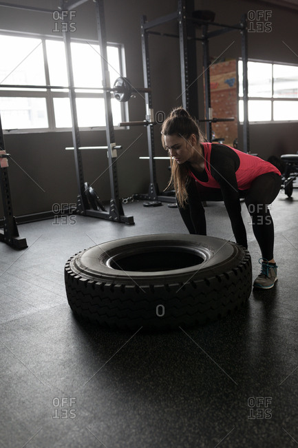 Fit woman exercising with tire in fitness studio