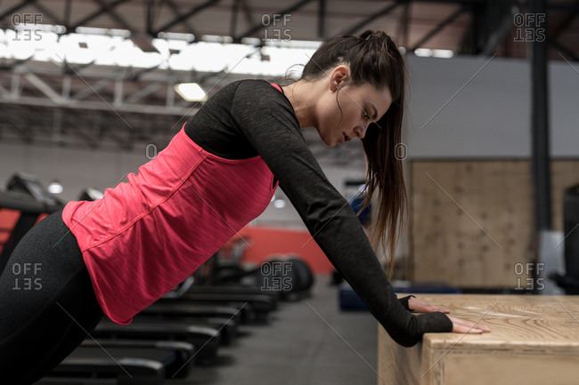 Fit woman doing push up exercise in fitness studio