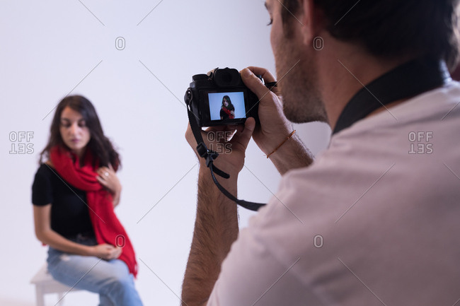 Male photographer clicking photos of model in photo studio