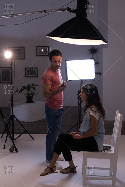 Male photographer recording an interview using voice recorder in photo studio