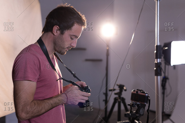 Male photographer reviewing photos on digital camera in photo studio