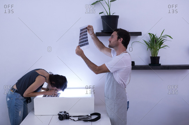 Male photographer and female model looking at negative filmstrip in photo studio