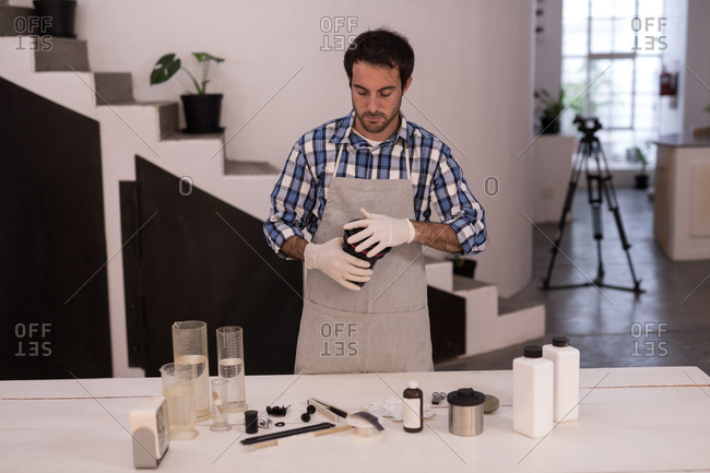 Male photographer opening a lens cover in photo studio
