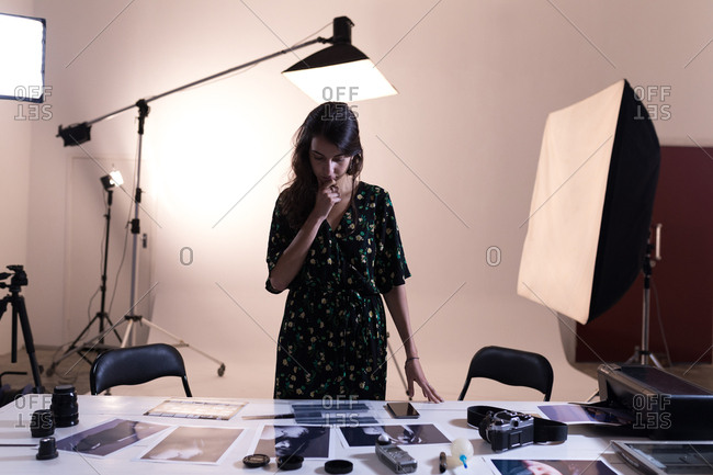 Female photographer looking at photographs in photo studio