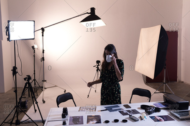 Female photographer having coffee while looking at photographs in photo studio