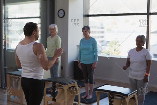 Trainer instructing group of senior women in yoga center