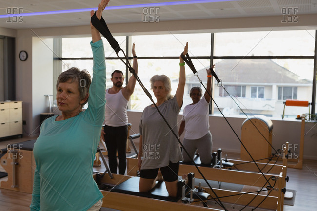 Group of senior women doing stretching exercise in yoga center