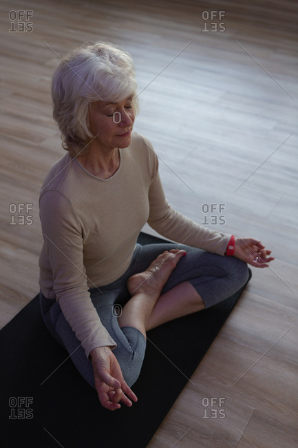 Senior woman performing yoga in yoga center