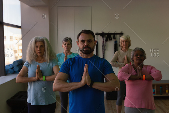 Trainer and group of senior women performing yoga in yoga center