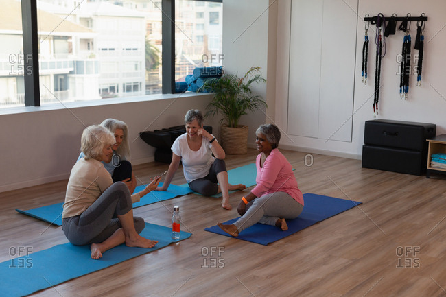 Group of senior women interacting with each other in yoga center