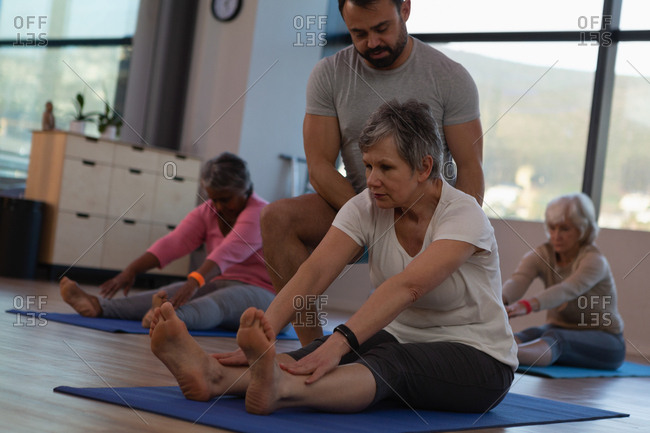 Trainer assisting senior women in performing yoga at yoga center