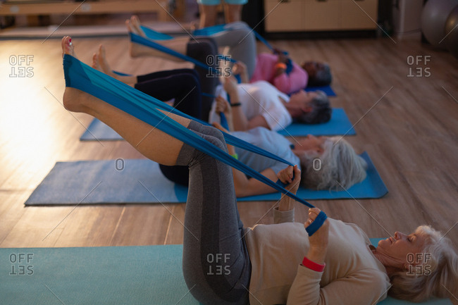 Group of senior women performing yoga with yoga band in yoga center