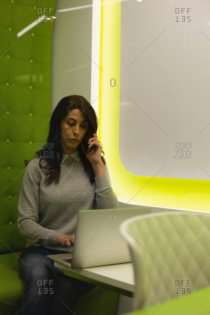 Businesswoman talking on mobile phone while using laptop at office
