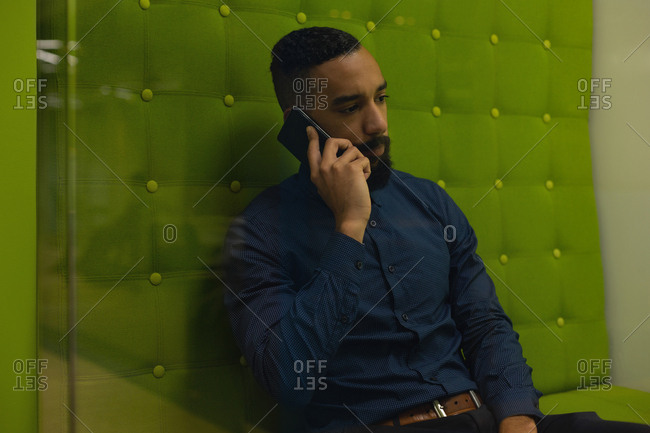 Businessman talking on mobile phone at office