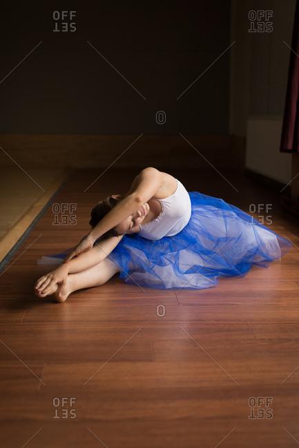 Ballerina practicing on wooden floor in studio