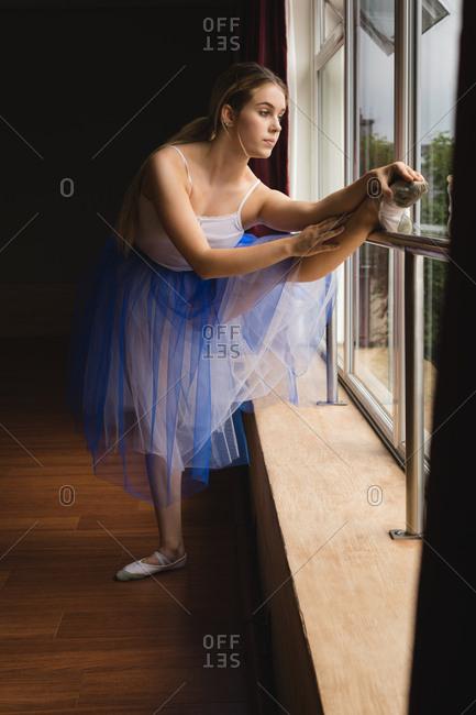 Ballerina practicing on the barre in dance studio