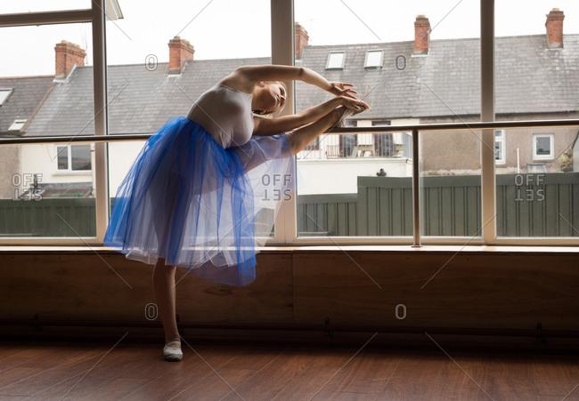 Ballerina practicing ballet dance near window in dance studio