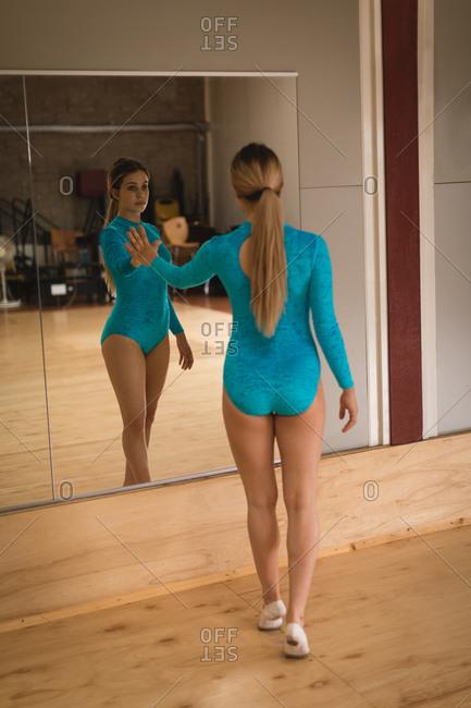 Beautiful ballerina looking at mirror in dance studio