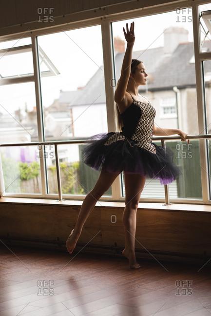Graceful ballerina practice arabesque ballet position in studio