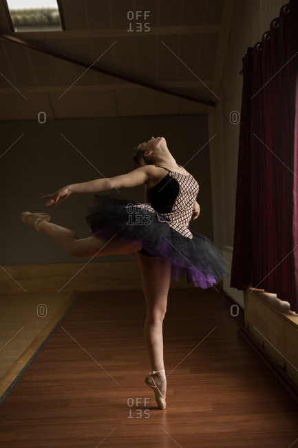 Graceful ballerina practice arabesque ballet position in studio