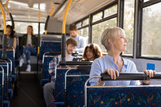 Female commuter looking through window while travelling in modern bus