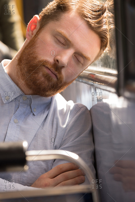 Close-up of male commuter sleeping while travelling in modern bus