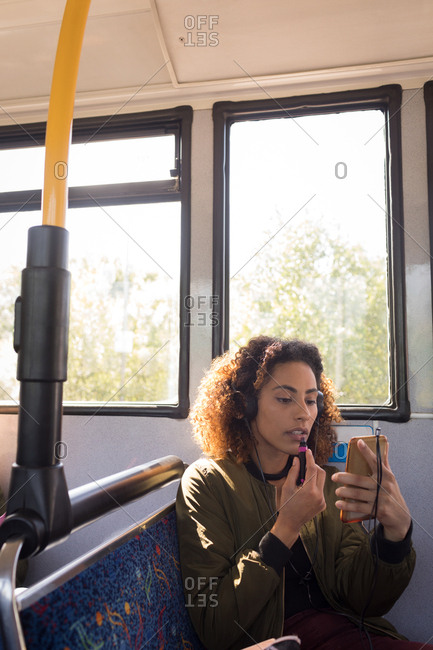 Young female commuter applying make up while travelling in modern bus