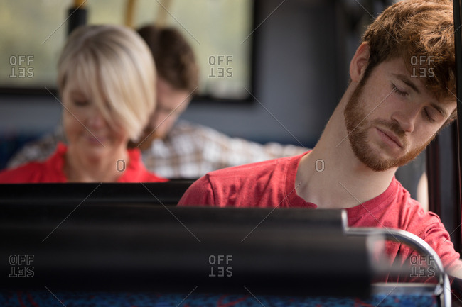 Male commuter sleeping while travelling in modern bus