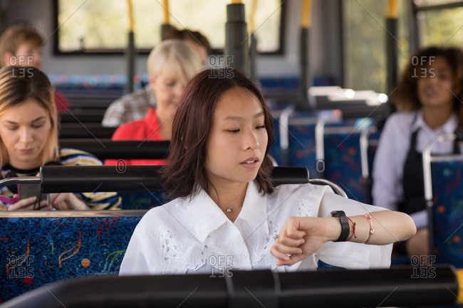 Beautiful female commuter checking time while travelling in modern bus