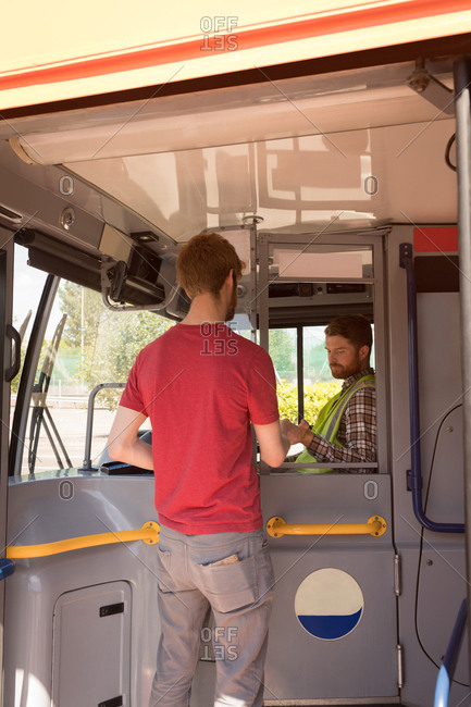 Young male commuter taking ticket from driver in modern bus