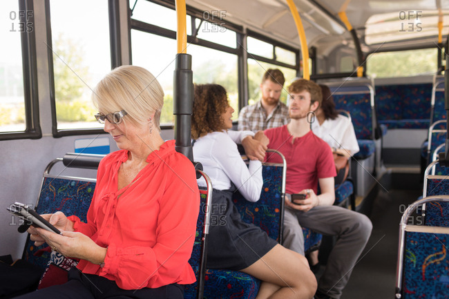 Female commuter using mobile phone while travelling in modern bus