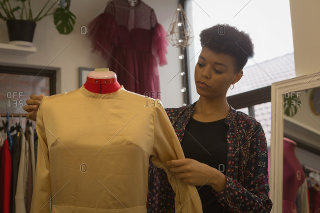 Fashion designer adjusting dress of mannequin in fashion studio