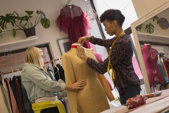 Fashion designer dressing mannequin in fashion studios