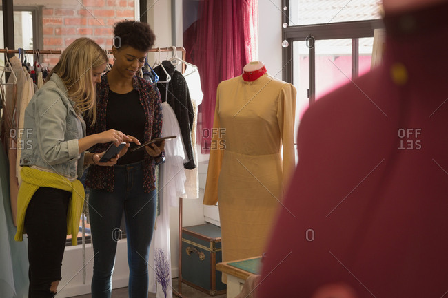 Fashion designers discussing on digital tablet in fashion studio