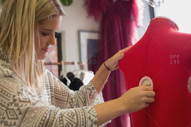 Fashion designer dressing mannequin in fashion studio