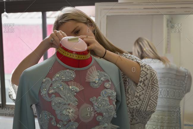 Fashion designer taking measurement of mannequin in fashion studio