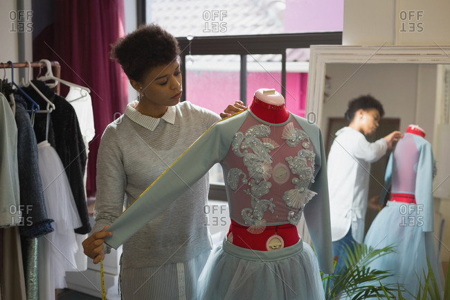 Fashion designer taking measurement of mannequin in fashion studio