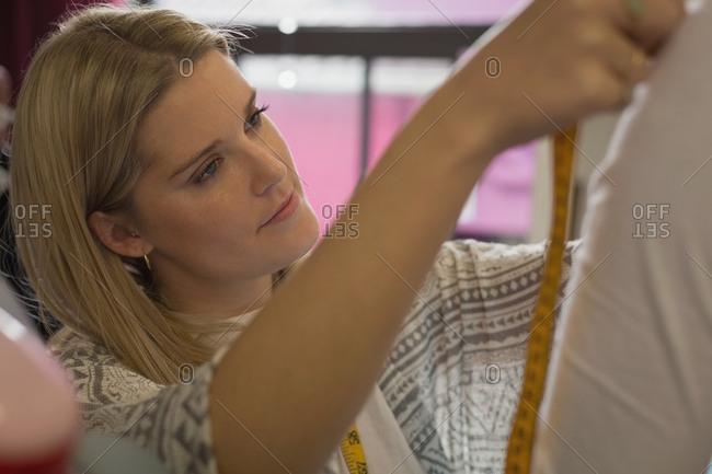 Beautiful fashion designer taking measurement in fashion studio